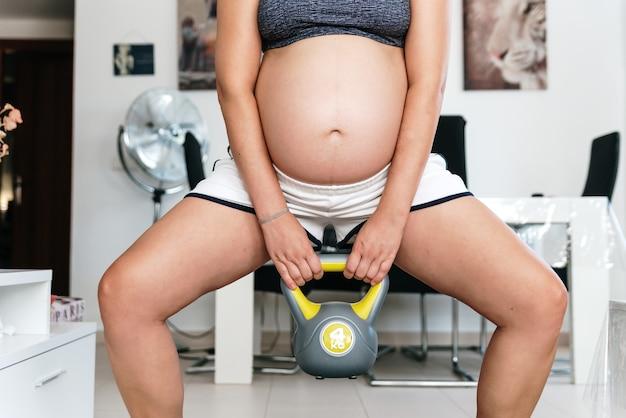 Беременная женщина делает приседания с гирей в гостиной.