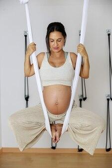 空中ヨガをしている妊婦