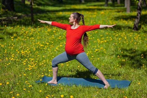 Беременная женщина делает асаны на открытом воздухе