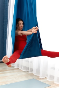 Pregnant woman doing exercises in an air hammock, anti-gravity yoga, strengthening the health of mom and future baby, training concept during pregnancy.