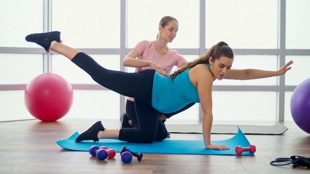 フィットネスクラスのパーソナルトレーナーと妊娠中の女性のためのエクササイズをしている妊娠中の女性。母性とスポーツ、あなたの体と健康の世話をします。
