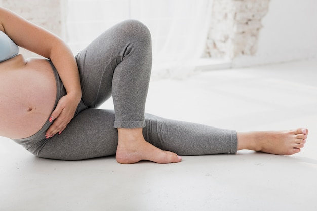 Pregnant woman doing exercises indoors