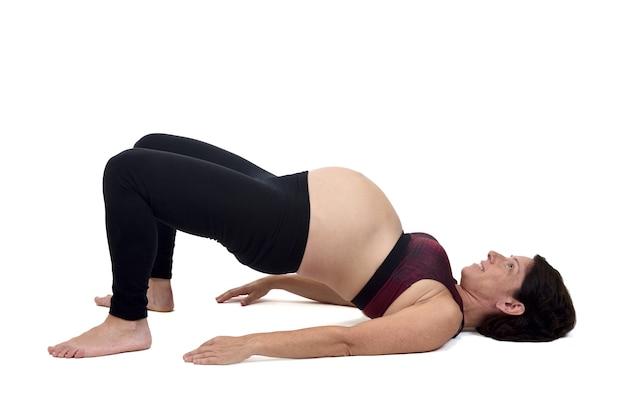 Беременная женщина делает упражнения на белом фоне