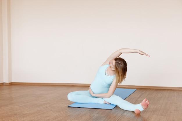 明るいスタジオでマットの上に座って運動をしている妊婦