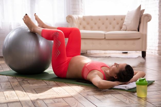 Pregnant woman doing exercising on yoga carpet.