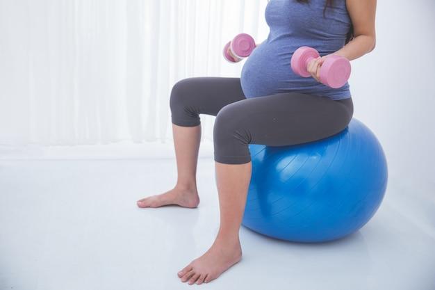 임신 한 여자는 요가 공에 exersice를 하 고