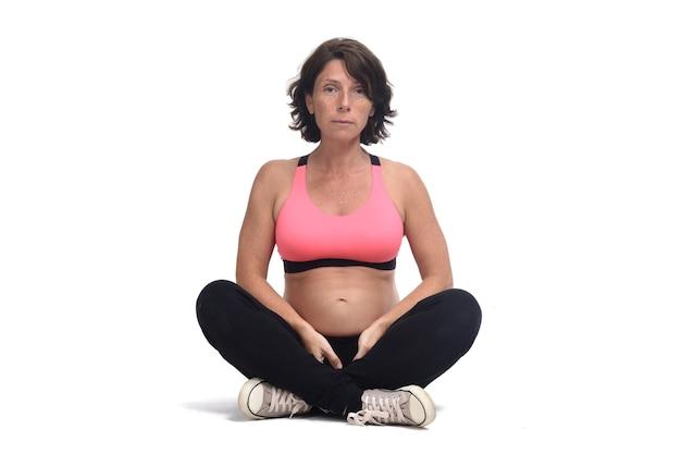 Беременная женщина делает вольные упражнения на белом фоне