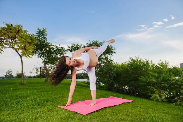 Pregnant woman doing prenatal yoga on nature.