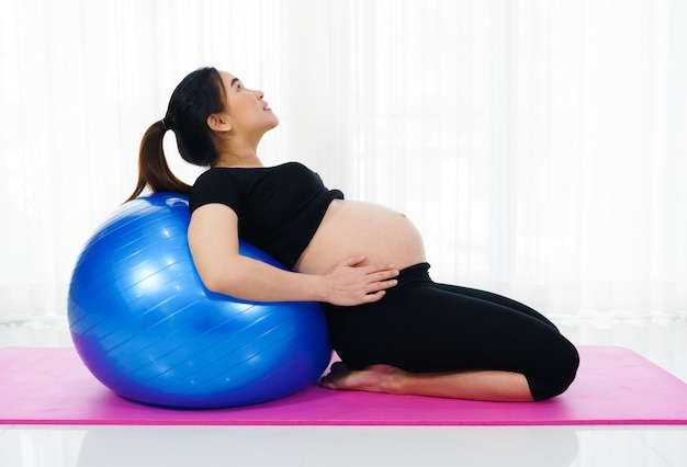 Pregnant woman doing yoga exercise on fitness ball in the living room at home