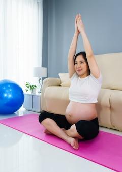 自宅の居間でヨガの練習をしている妊婦