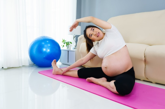 Pregnant woman doing yoga exercise in the living room at home