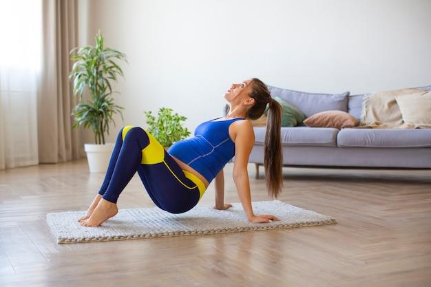 Беременная женщина занимается йогой в домашнем интерьере на полу.