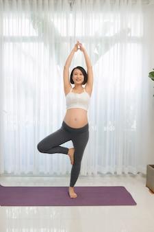 妊娠中の女性がリビングルームでヨガをやって