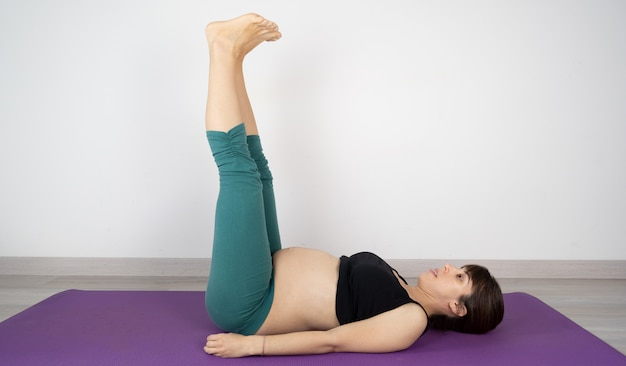 Pregnant woman doing yoga postures on a mat