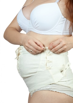 Pregnant woman dressing maternity belt