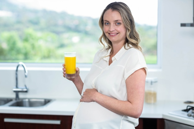 Pregnant woman drinking a glass of orange juice in the kitchen