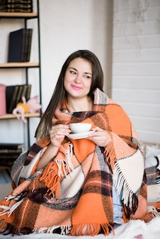 Беременная женщина пьет чай в постели у себя дома