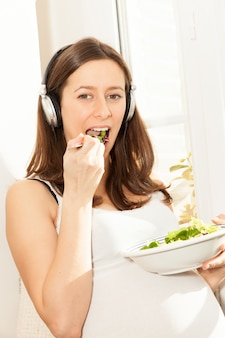 Pregnant woman eat salad and listening to music