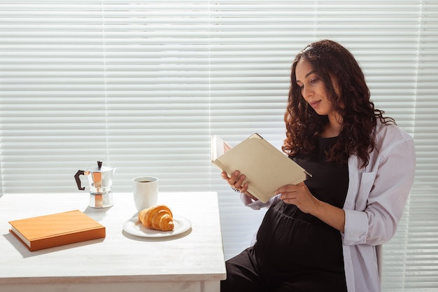 妊娠中の女性が家で本を食べたり読んだりします。朝、朝食、妊娠のコンセプト。
