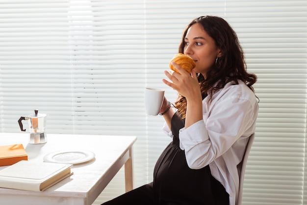 아침을 먹는 임산부. 임신 및 출산 휴가.