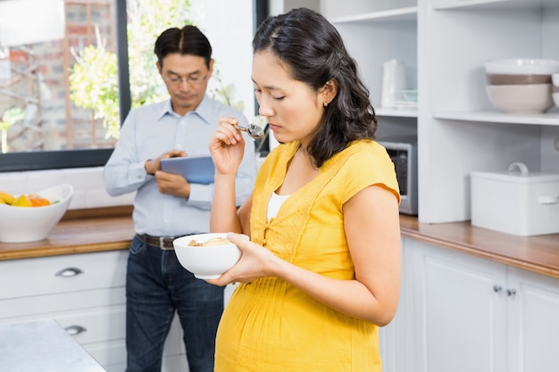 Pregnant woman eating cereals in the kitchen