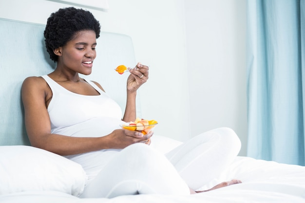 Pregnant woman eating fruit salad lying on her bed
