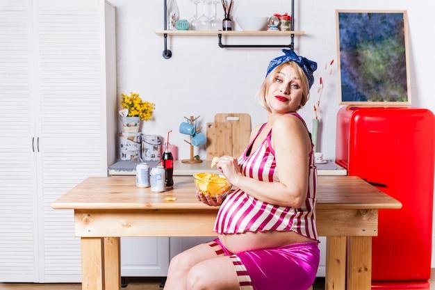 감자 칩을 먹는 임신 한 여자
