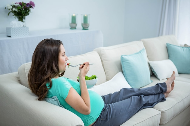 Pregnant woman eating salad on couch