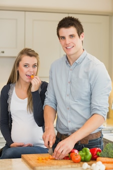 Pregnant woman eating vegetables prepared by husband