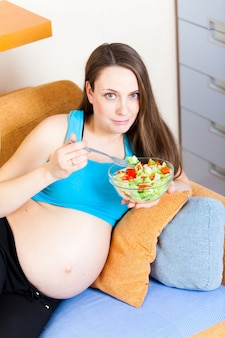 Pregnant woman eats a salad lying on the sofa