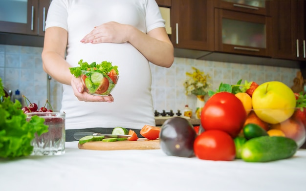 A pregnant woman eats vegetables and fruits
