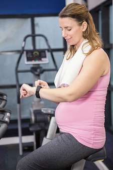 Pregnant woman on exercise bike using smartwatch at the gym