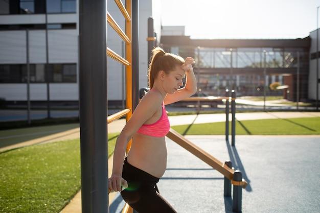 屋外で一人で運動する妊婦