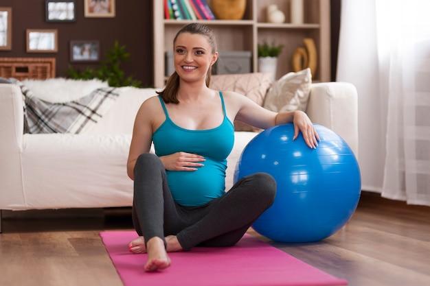 Беременная женщина, тренирующаяся дома