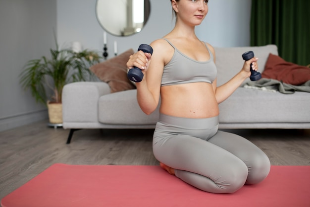 Donna incinta che si esercita a casa