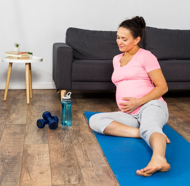 Pregnant woman exercising on mat with weights and water bottle