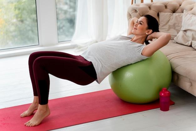 フィットネスボールで運動している妊婦