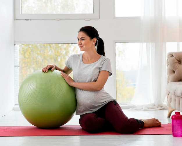 Pregnant woman exercising with green fitness ball