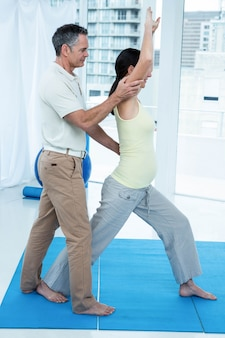 Pregnant woman exercising with physiotherapist at home