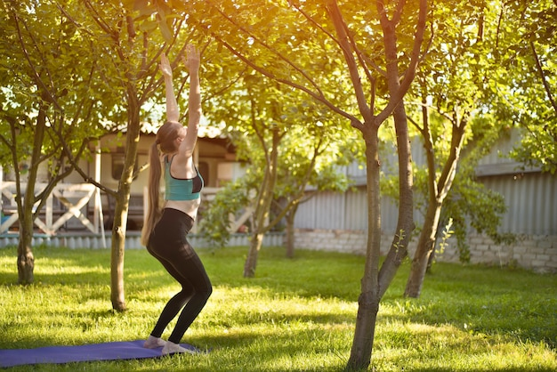 Pregnant woman in the garden practices yoga, greeting the sun