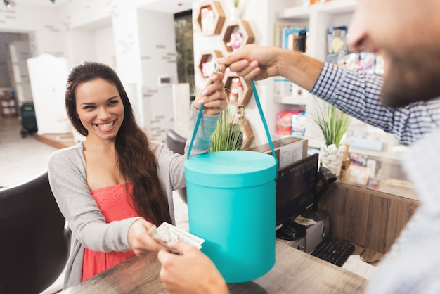 임신 한 여자는 가게에서 판매자에게 돈을 준다.
