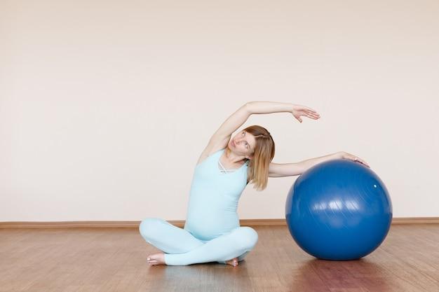 妊娠中の女性がスタジオでフィットネスボールを持ってスポーツに行く