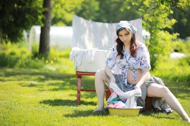 乾燥のためにロープに洗濯物をぶら下げている妊婦
