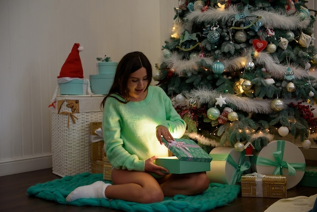Pregnant woman happy at home near the christmas tree during the christmas celebration.