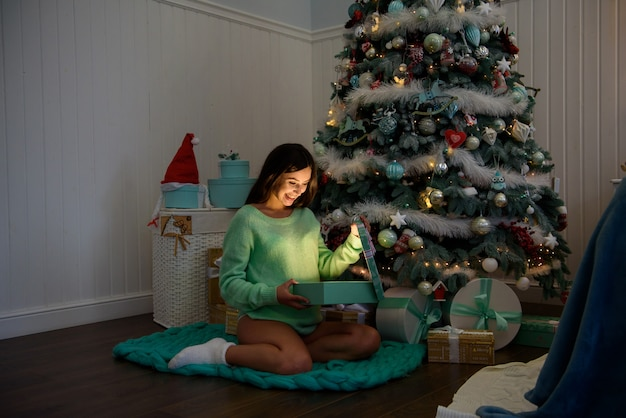 Pregnant woman happy at home near the christmas tree during the christmas celebration