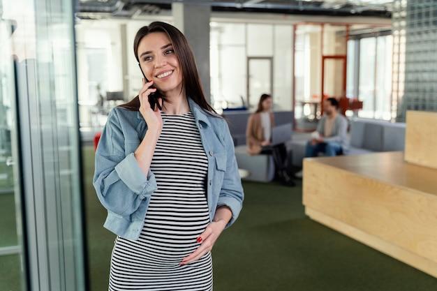 職場で電話をしている妊婦