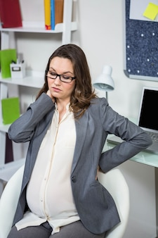 Pregnant woman having a back pain in home office