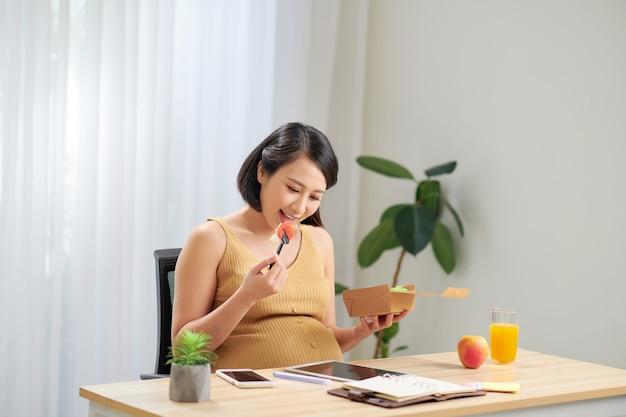 임신 한 여자 건강 샐러드를 먹고 집에서 휴식하는 동안 태블릿을 사용합니다.