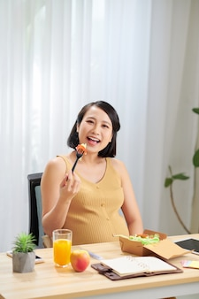 Pregnant woman healthy eating salad and using tablet while relaxing at home.