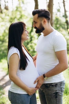 Pregnant woman and her beaeded husband hugging on the tummy together in nature outdoor